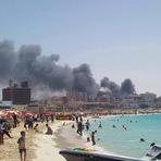 Internacional - Foto de egípcios na praia enquanto a cidade está pegando fogo